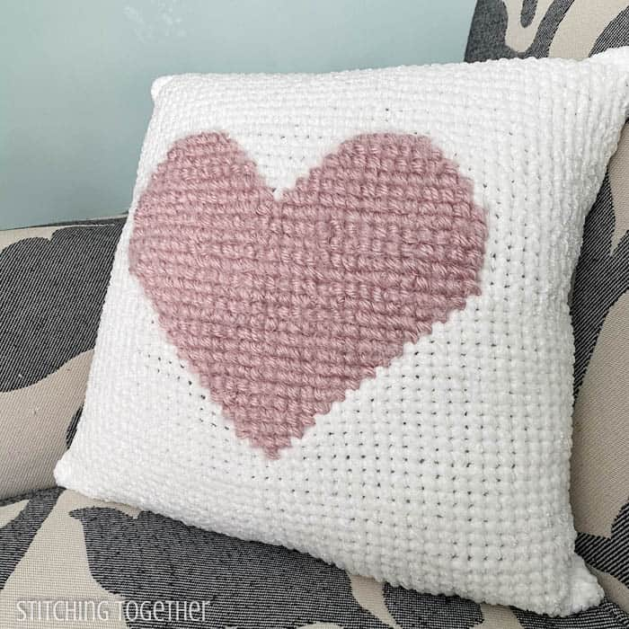 white and pink heart crochet pillow sitting on a chair