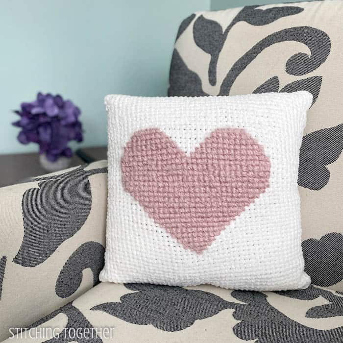 White crochet heart pillow sitting on a chair