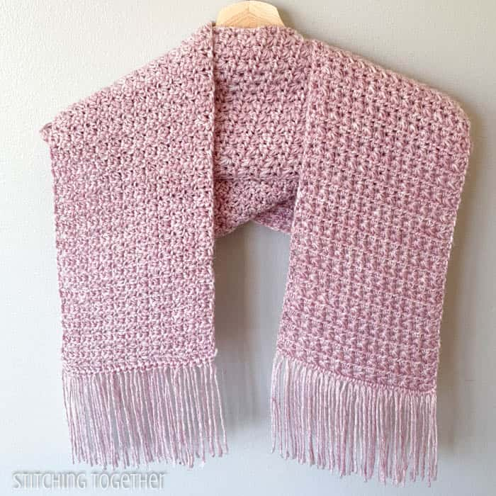 pink crochet scarf with fringe hanging