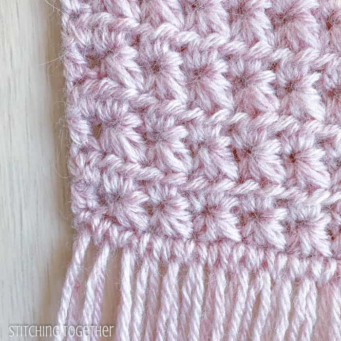close up of star like crochet stitches in pink yarn