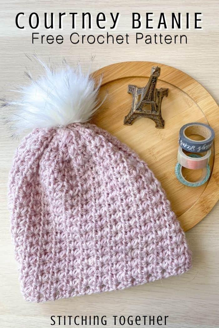 pink crochet beanie with white pom pom laying flat