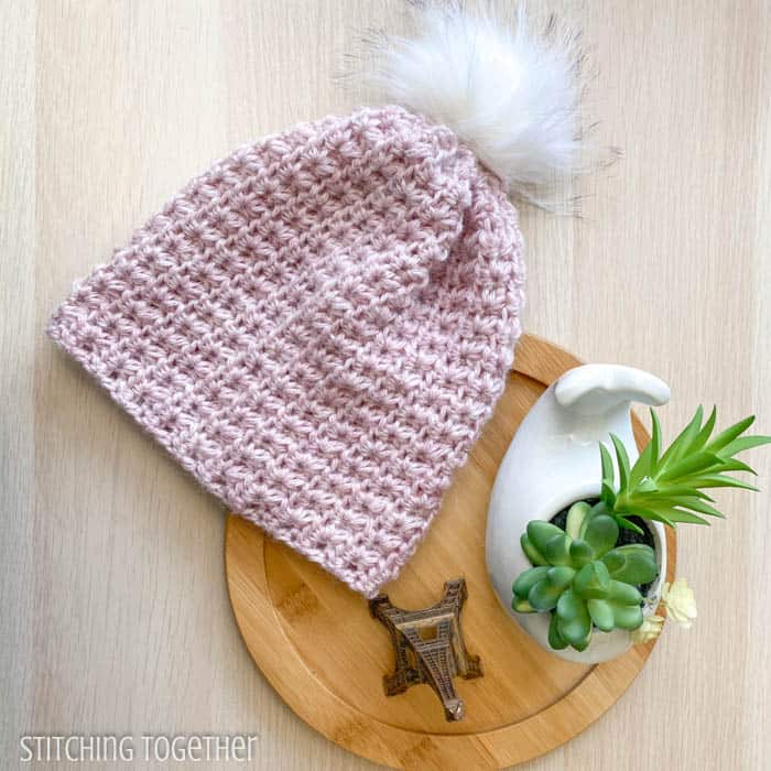 pink crochet beanie with pom pom flat lay