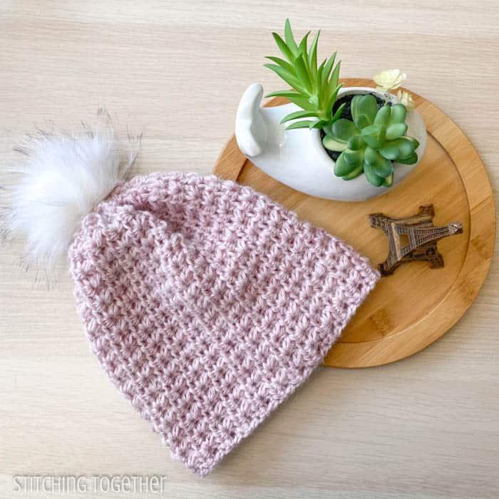 pink crochet beanie hat with pom pom flat lay