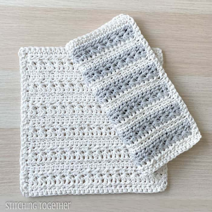 2 crochet dishcloths one folded and with striped laying on top of a cream dishcloth