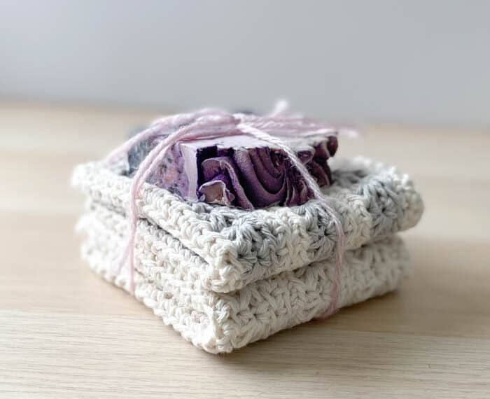 two crochet washcloths folded and stacked with a bar of soap on the top