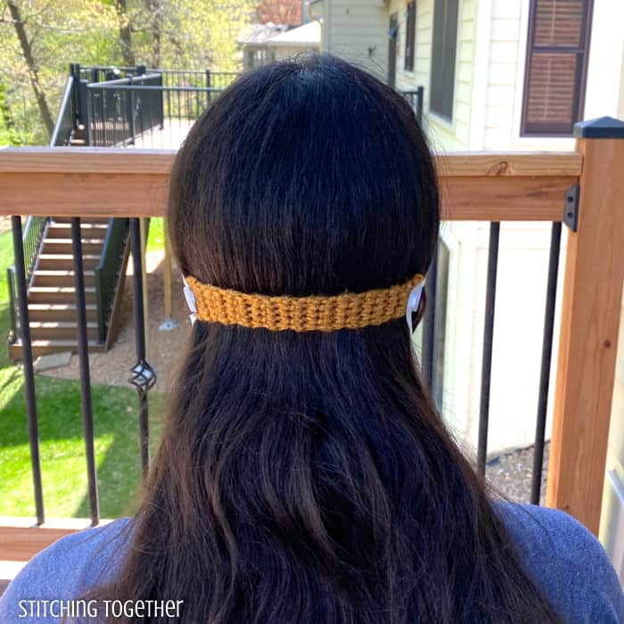 back of head view of lady wearing crochet ear saver for mask
