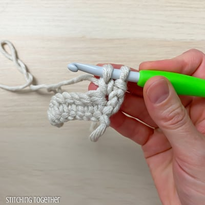 hand holding yarn and a crochet hook showing the steps of a stitch