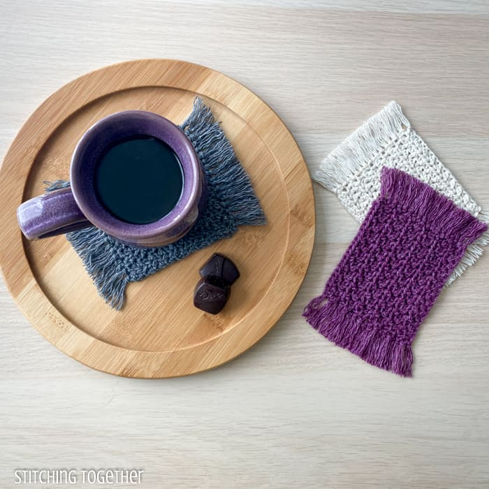 mug sitting on a crochet coaster with 2 other coasters stacked near the mug