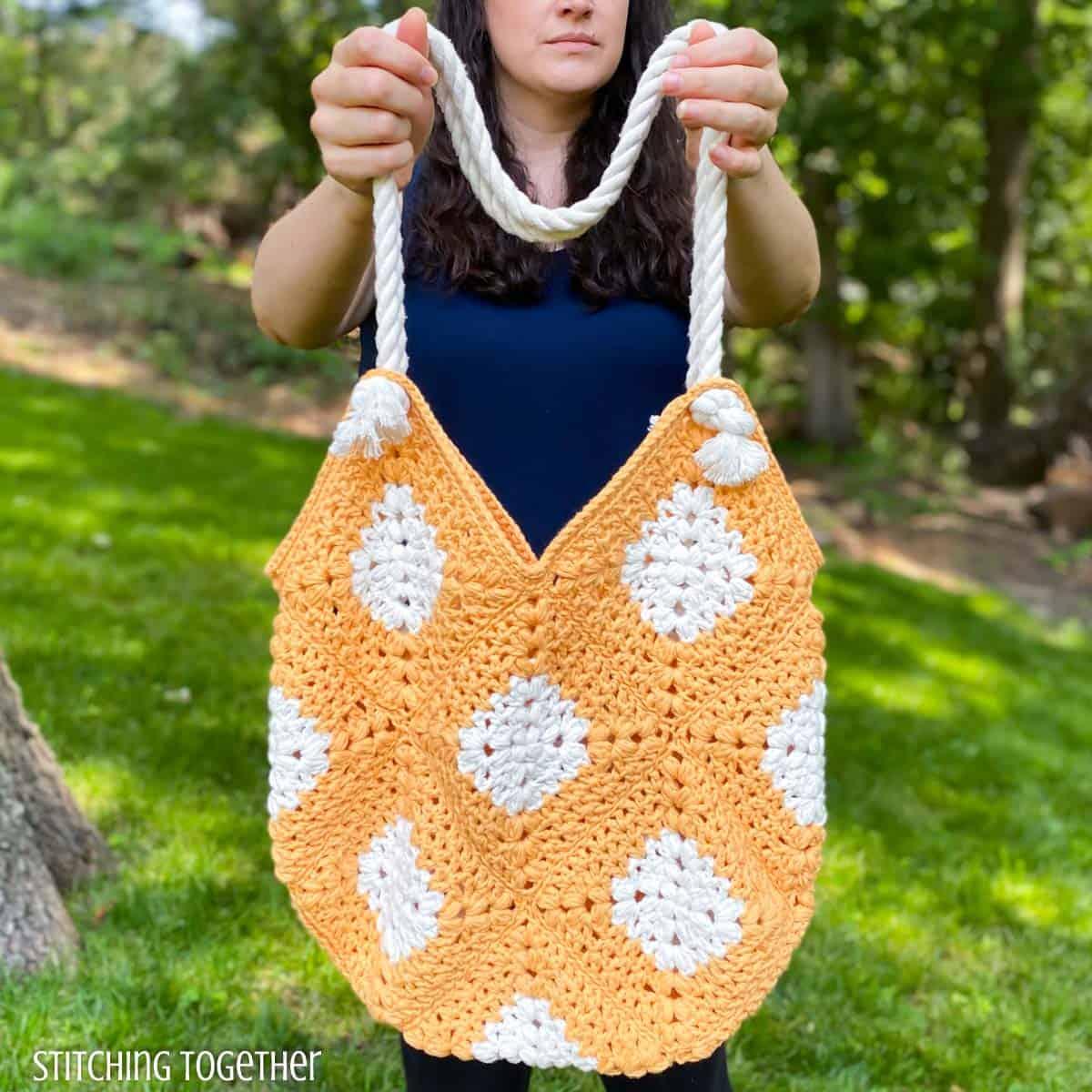 lady holding orange and white crochet market bag