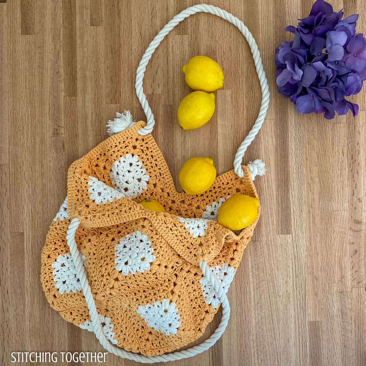 crochet market bag on a counter with lemons and flowers
