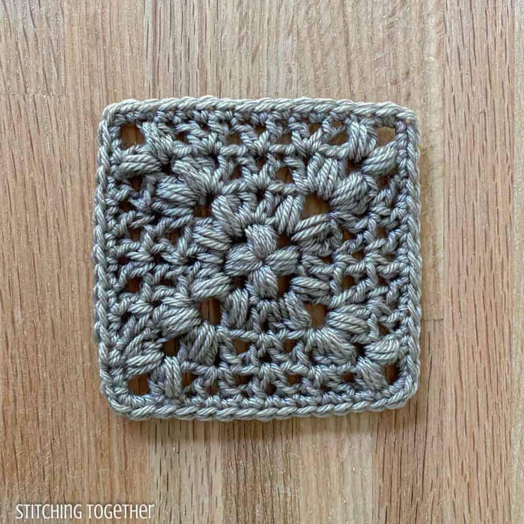 gray crochet granny square with puff stitches and v stitches