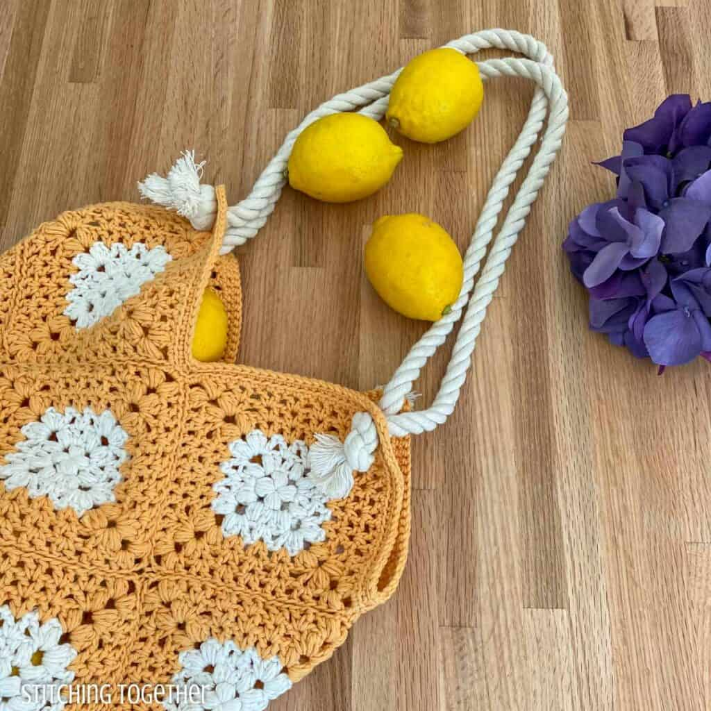 crochet market tote on a counter with lemons and flowers