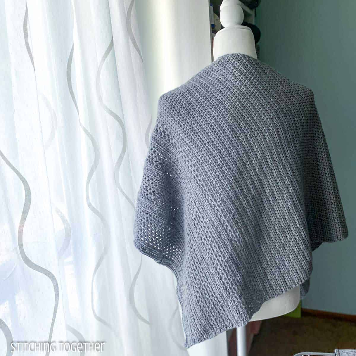 crochet shawl on a mannequin facing away