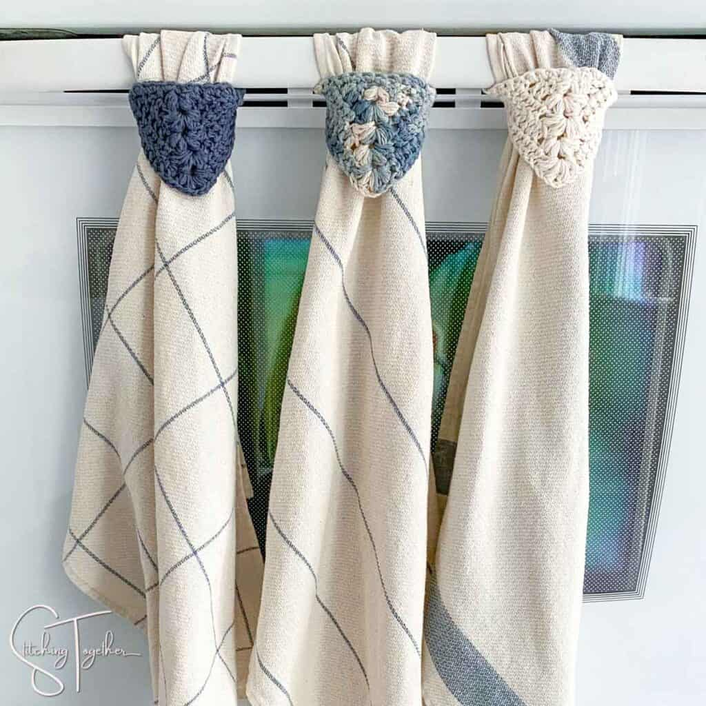 3 crochet towel toppers hanging from oven