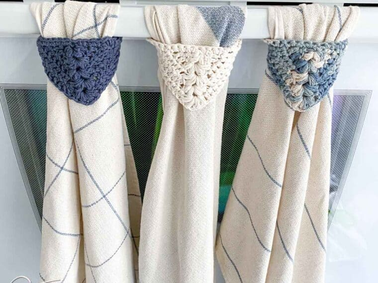 3 dishtowels hanging on an oven by crochet towel hangers