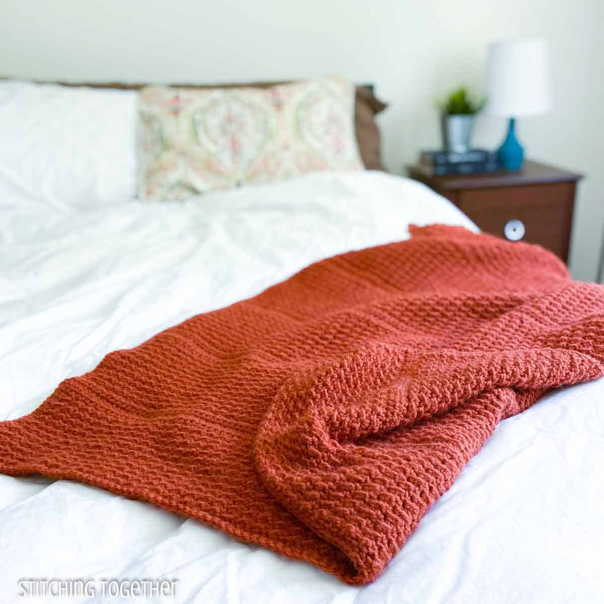 terracotta crochet lap throw draped on a bed