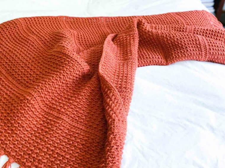 orange crochet throw blanket draped on a bed