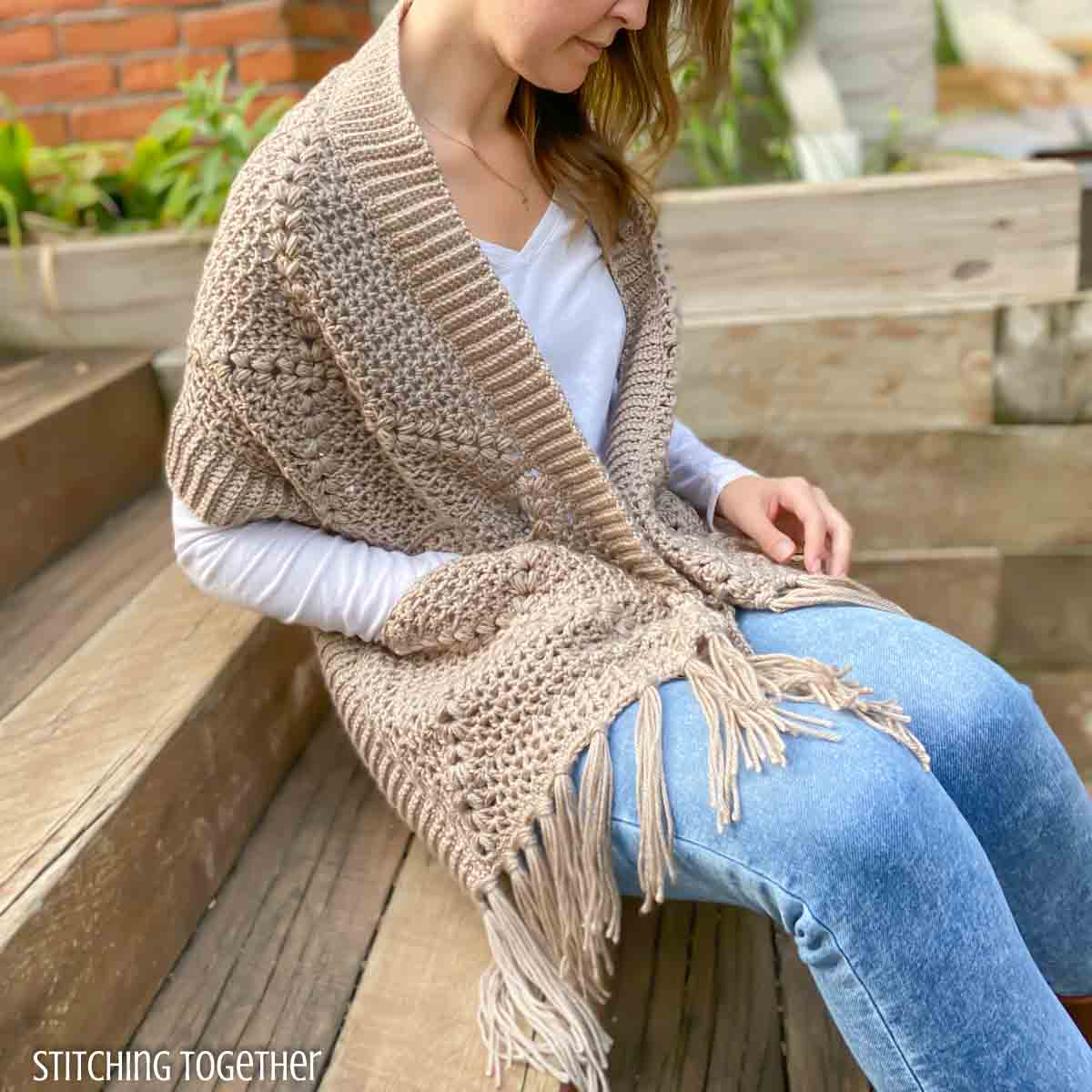woman sitting on steps while wrapped in a crochet wrap with pockets