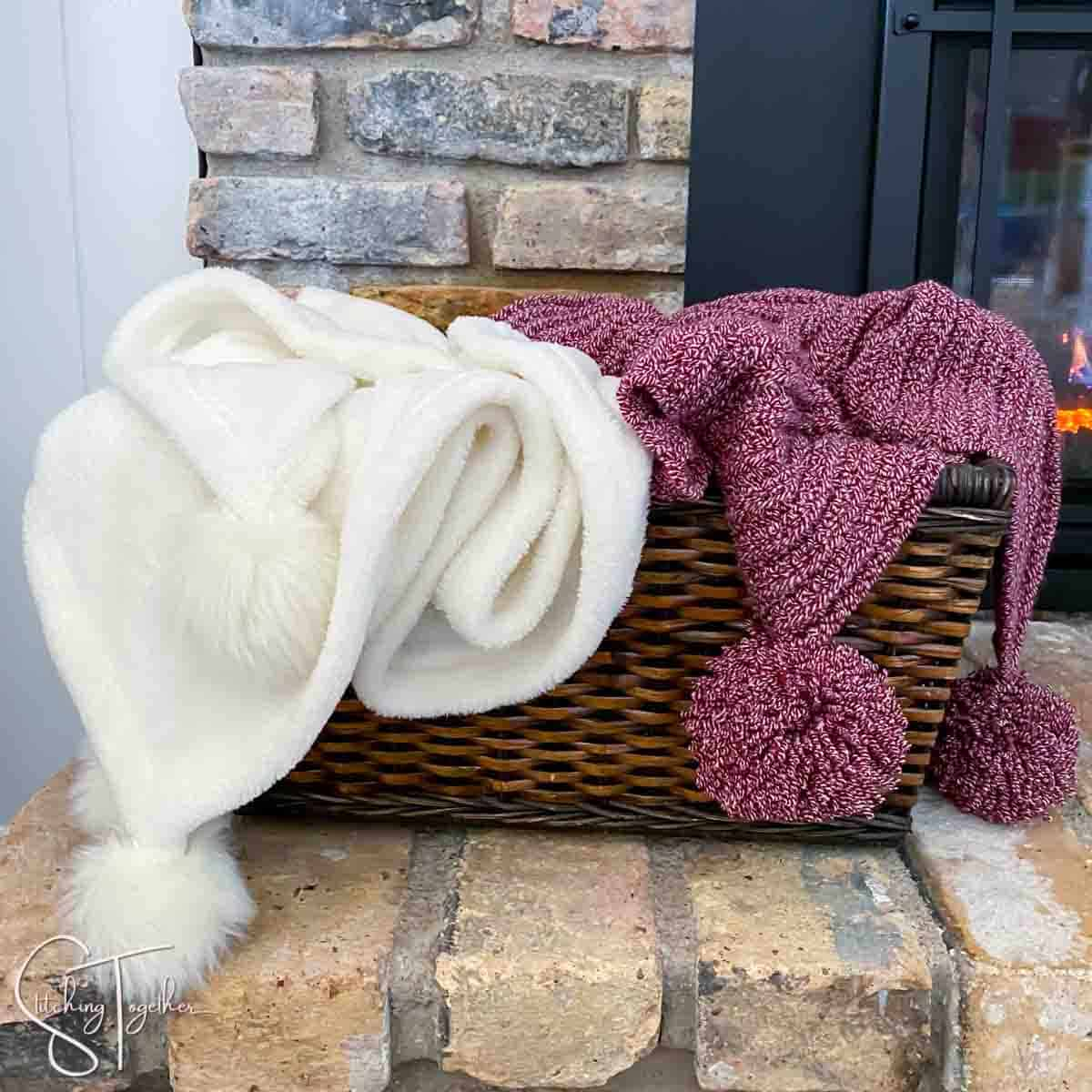 a white blanket and a red crochet christmas blanket both with pom poms in a basket