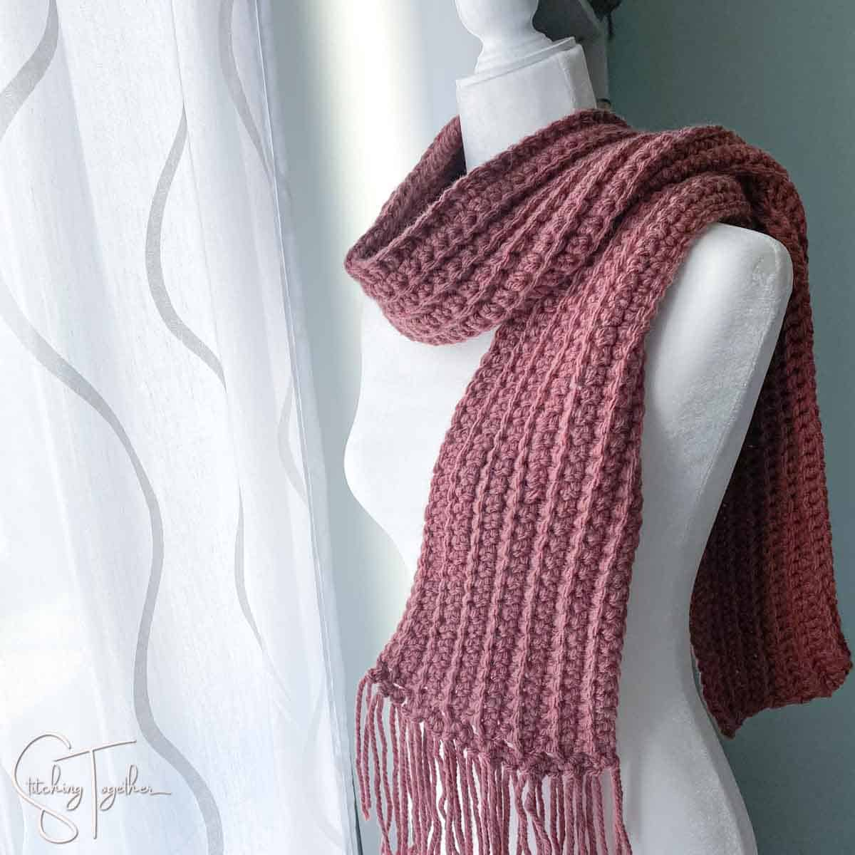 purple bulky crochet scarf on a mannequin