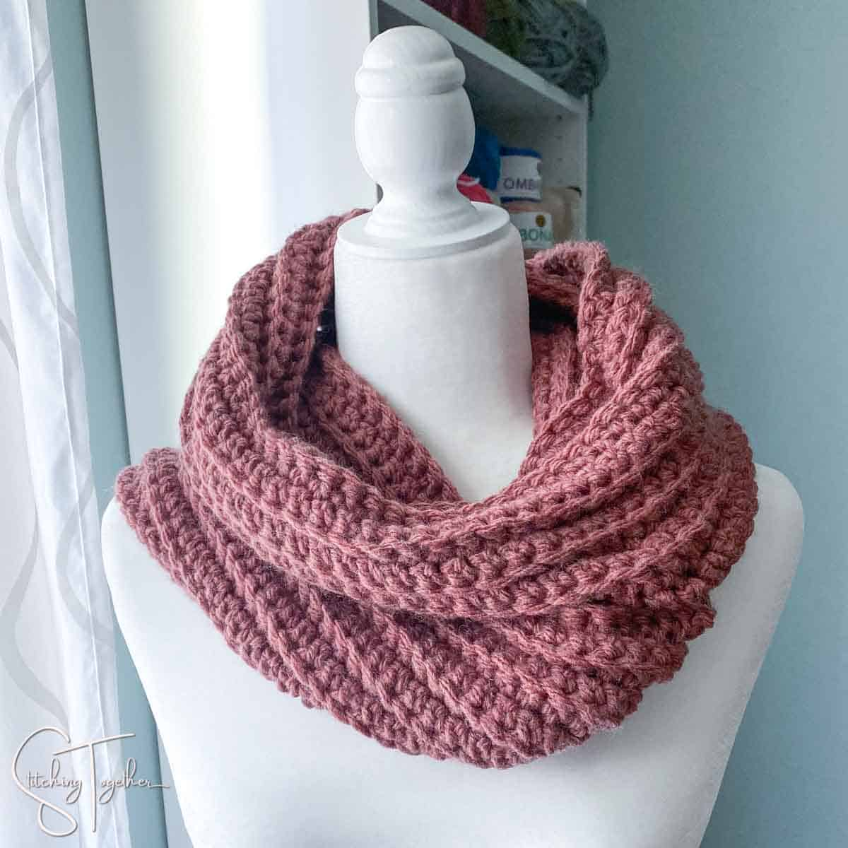 purple wrapped crochet scarf on a mannequin