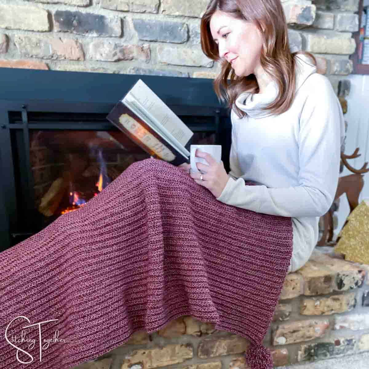 lady draped in a red and white crochet christmas blanket while reading in front of a fireplace