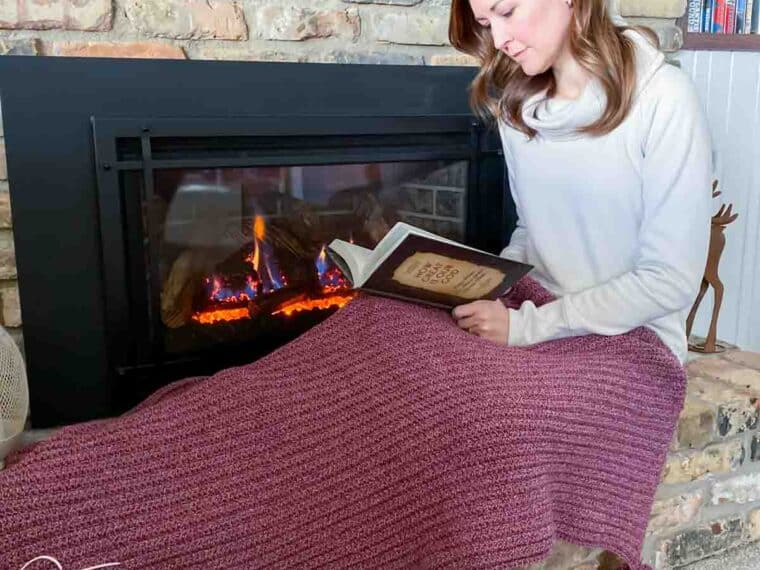 lady covered in a simple crochet christmas blanket while reading in front of a fireplace