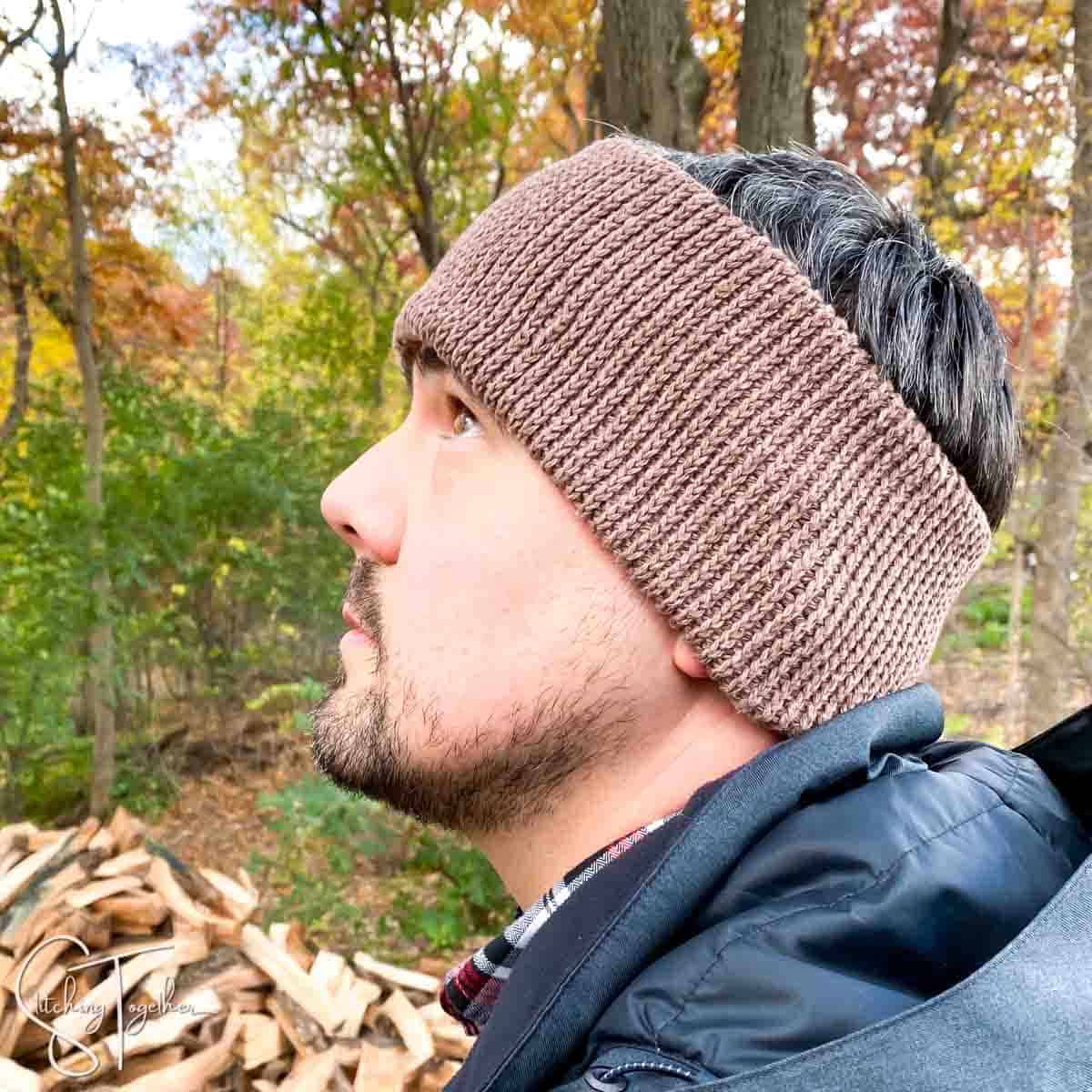 man wearing a brown crochet ear warmer and black jacket