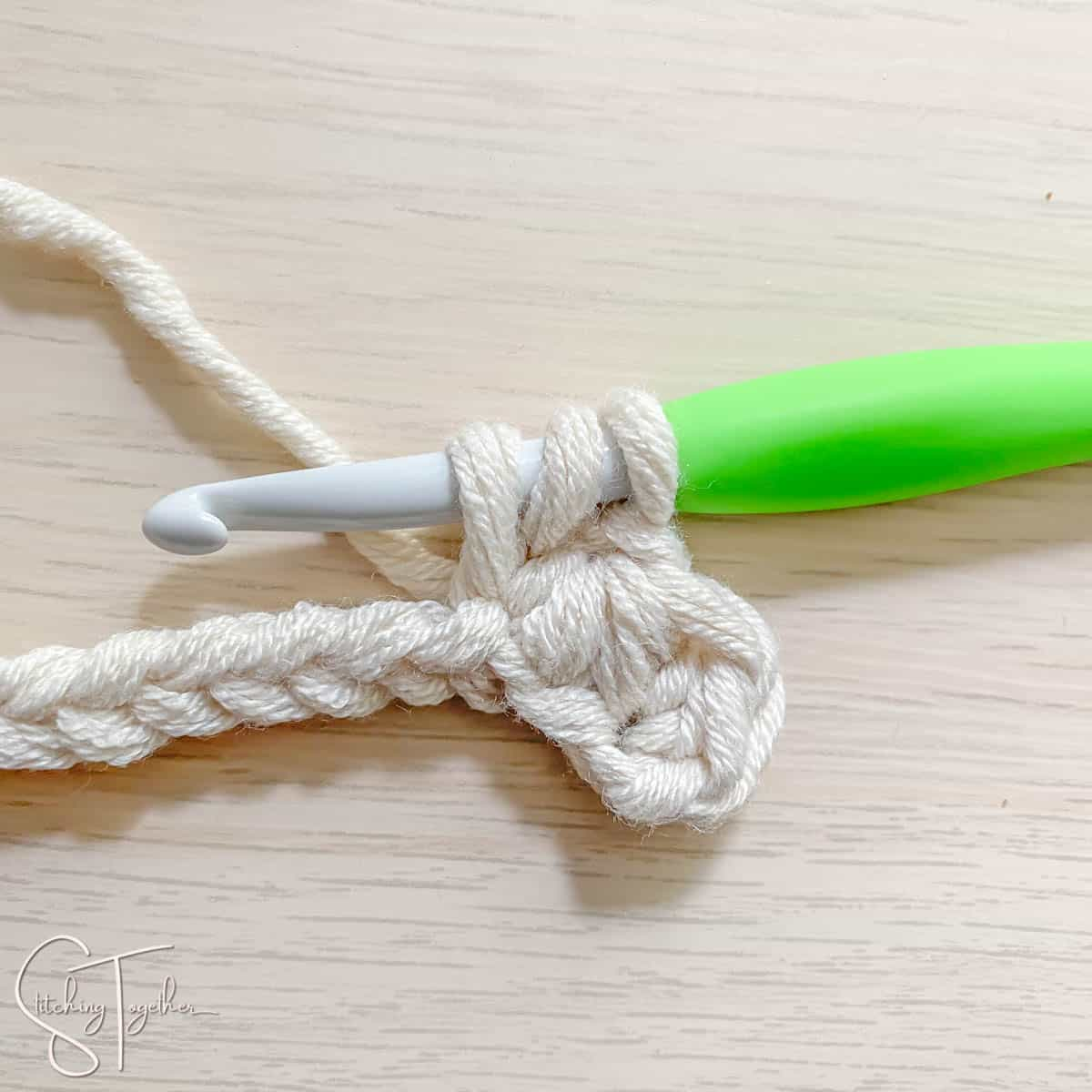 crochet hook and yarn showing the steps for a mhdc3tog