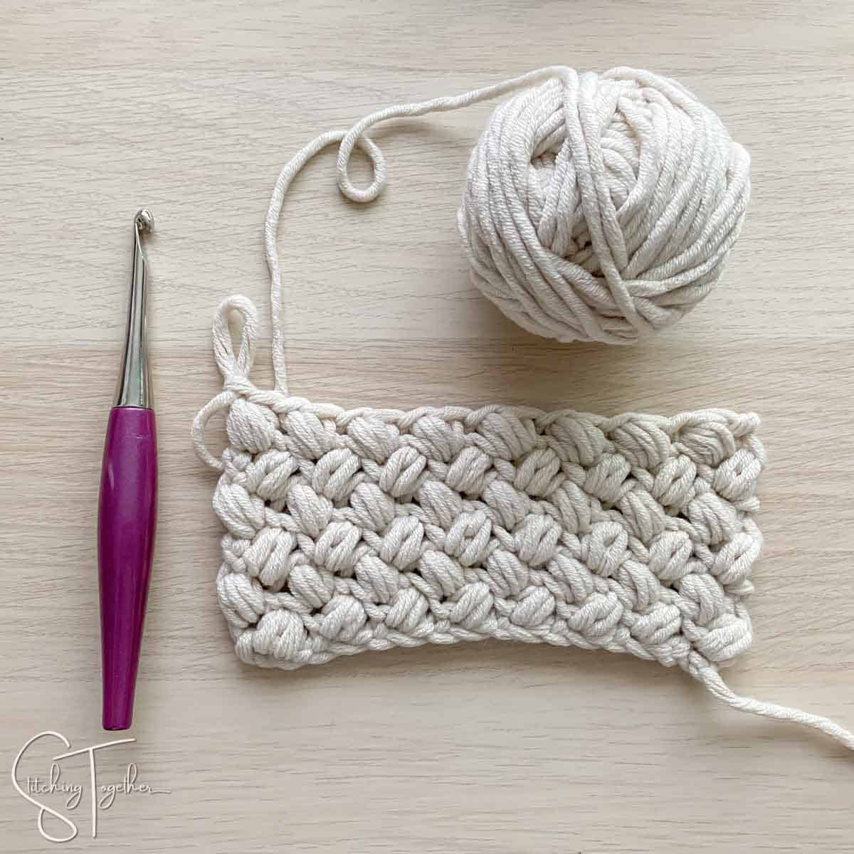 ball of yarn, hook, and bean stitch swatch