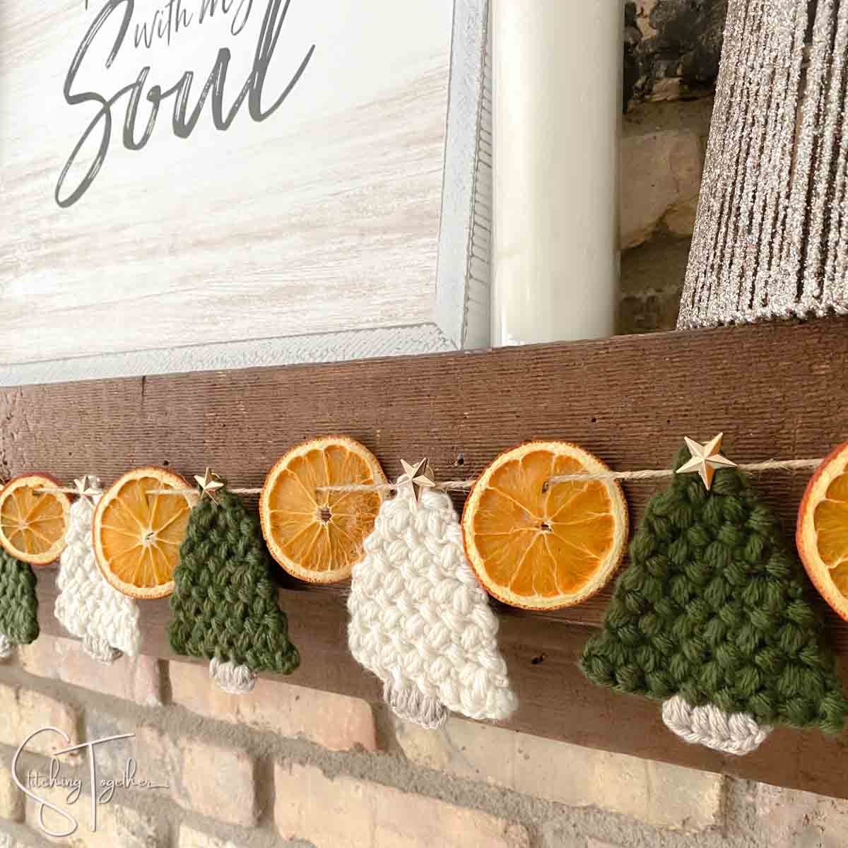 dried orange and crochet christmas tree garland on a fireplace mantle