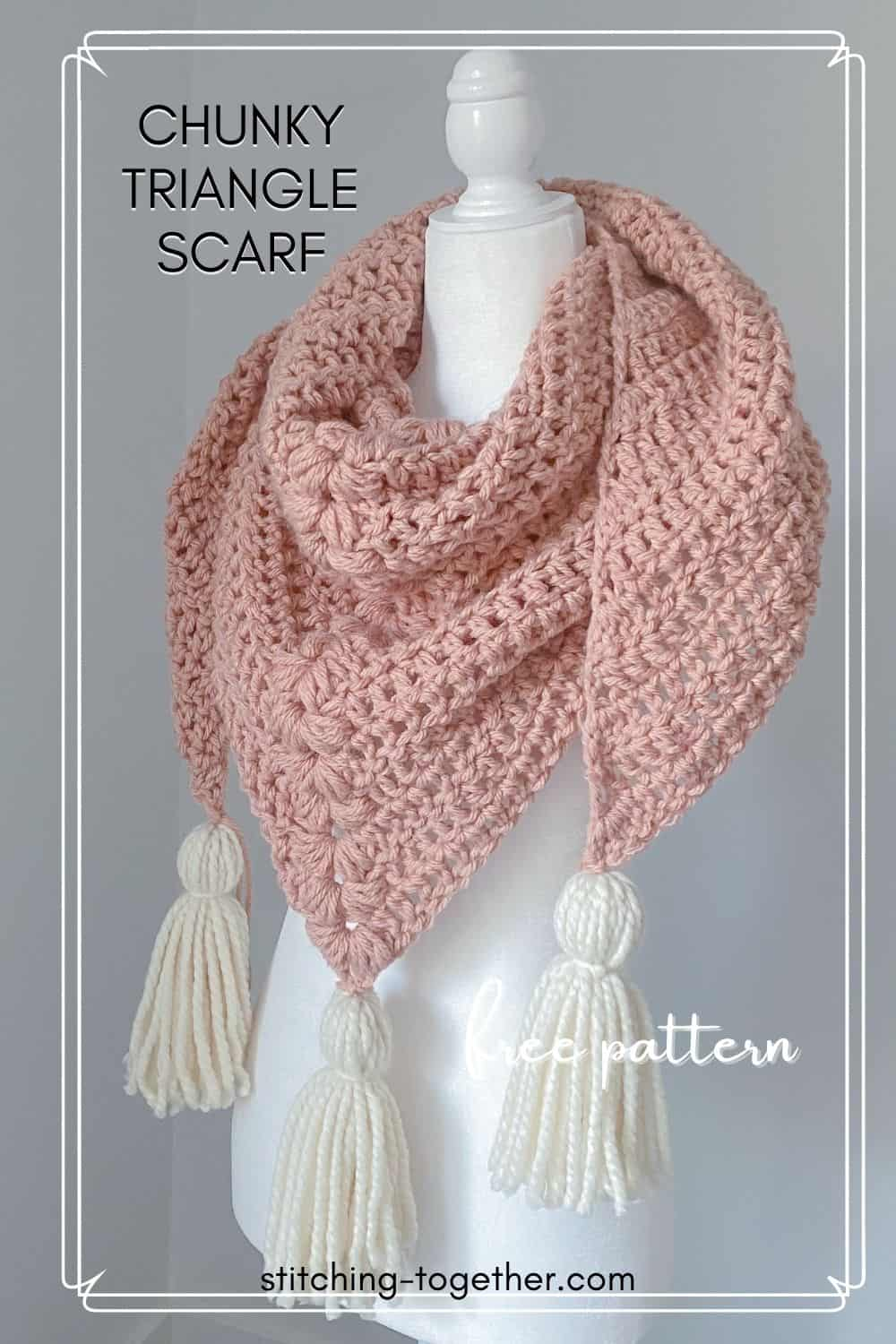 chunky crochet triangle scarf with white tassel on a mannequin