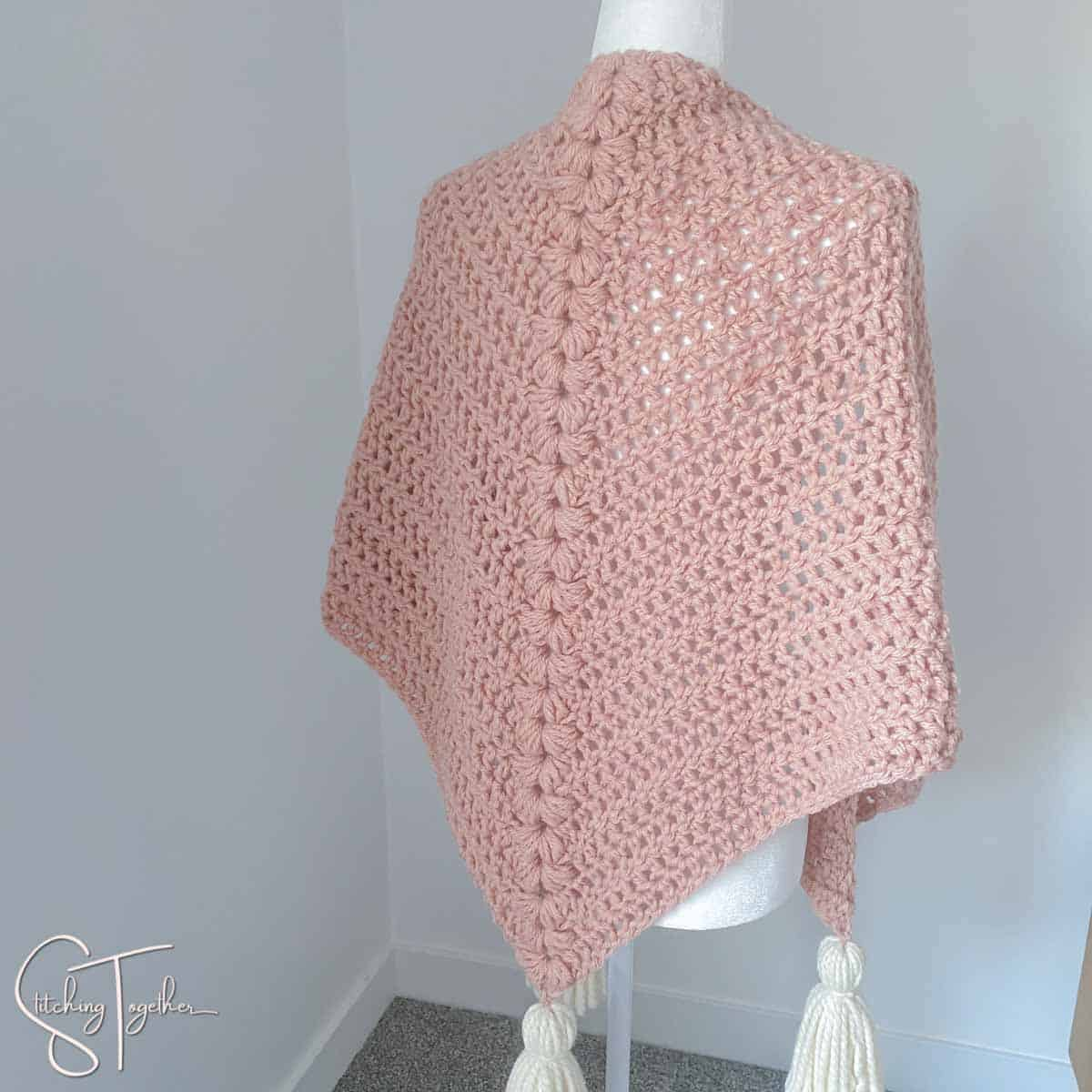 pink chunky triangle shawl with white tassel on a mannequin