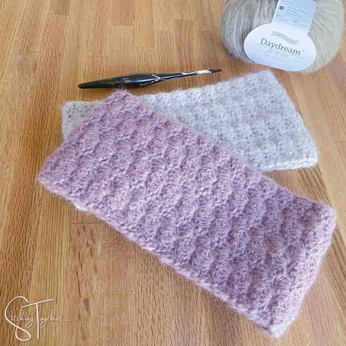 2 shell stitch crochet headbands laying flat near a hook and yarn