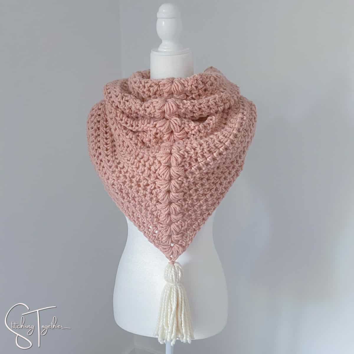 pink chunky triangle scarf with white tassel on a mannequin