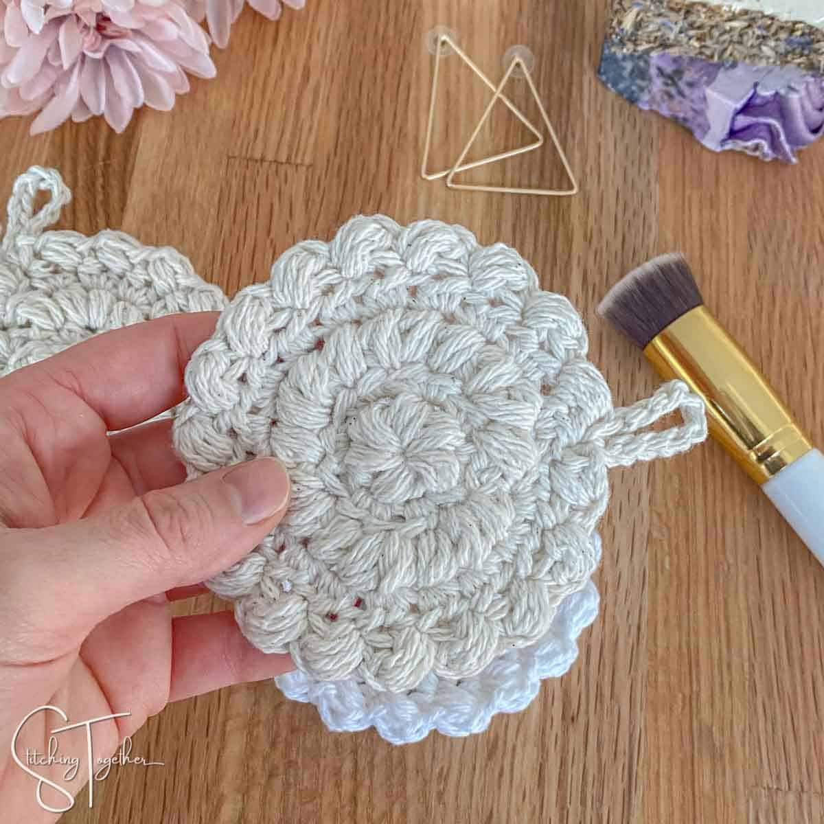a hand holding a crochet cotton face pad with accessories in the background