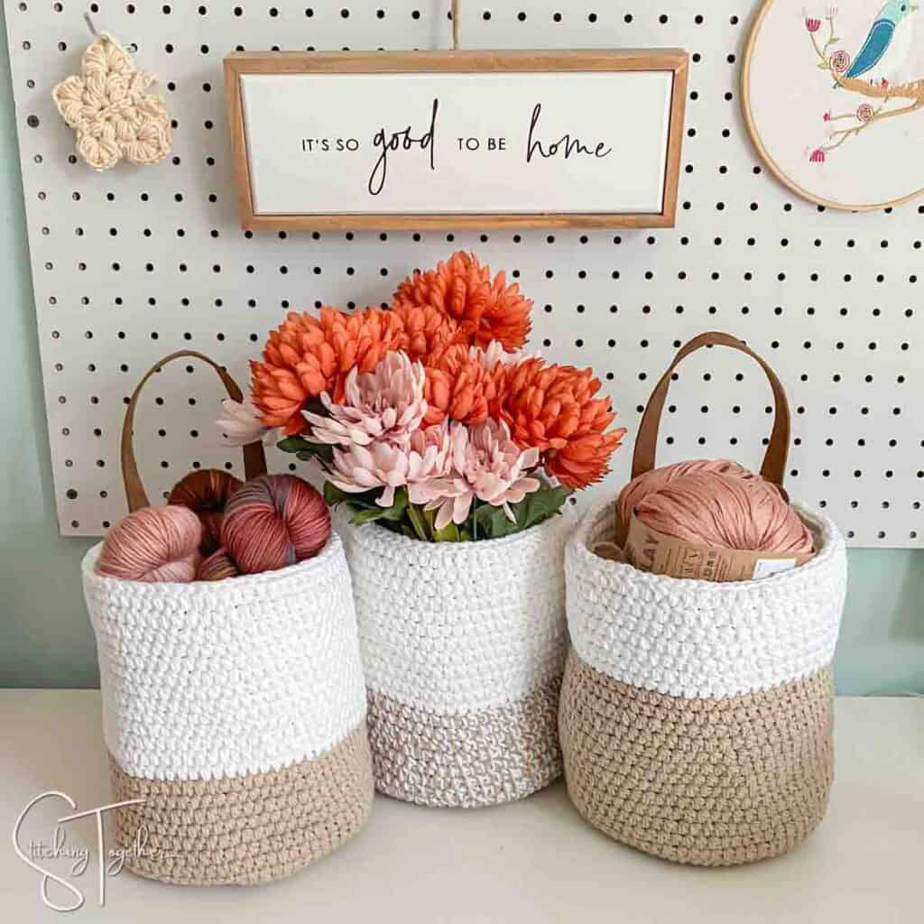 3 crochet baskets sitting on a shelf filled with yarn or flowers