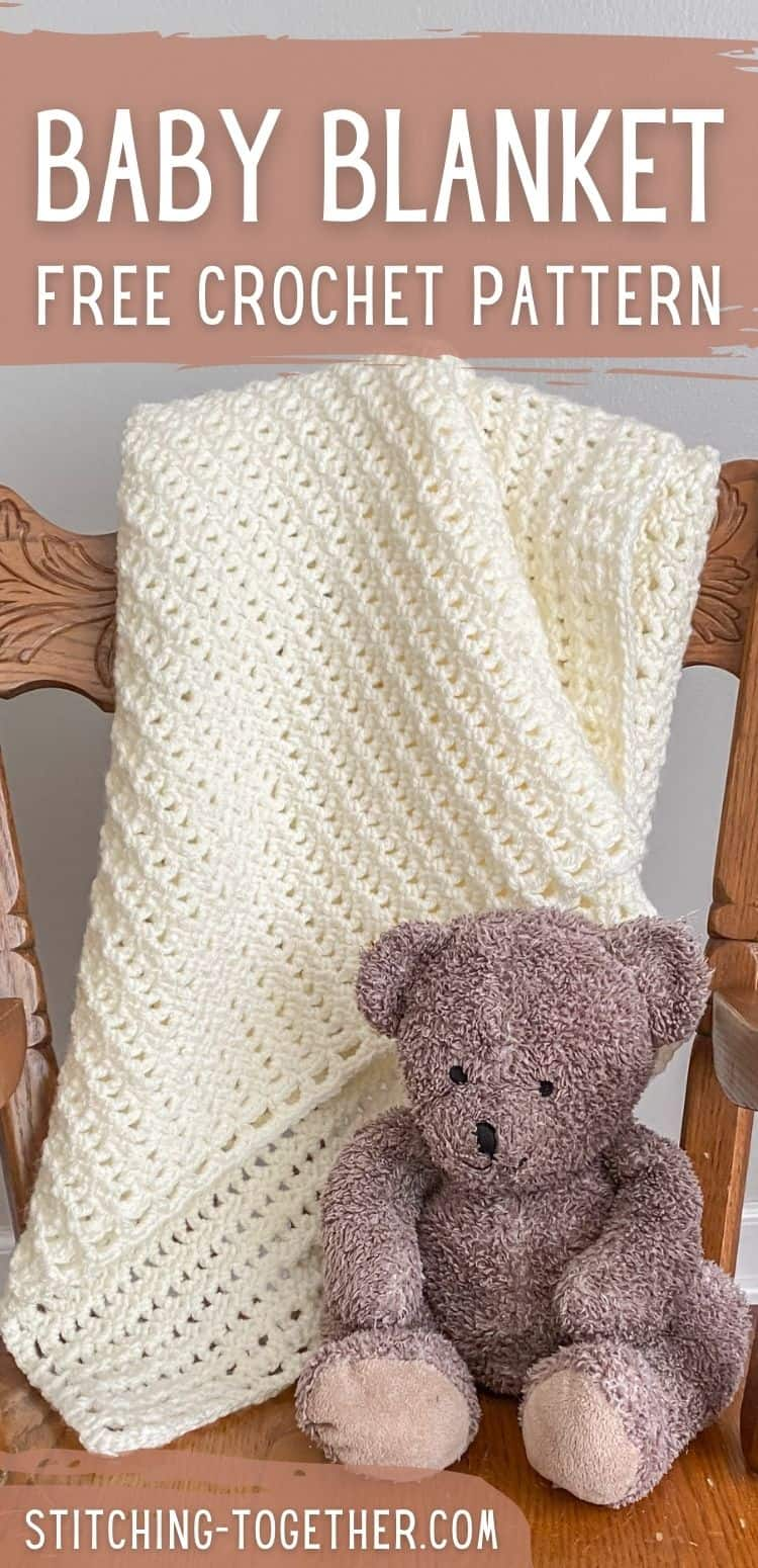 crochet lace baby blanket draped on chair with stuffed bear next to it