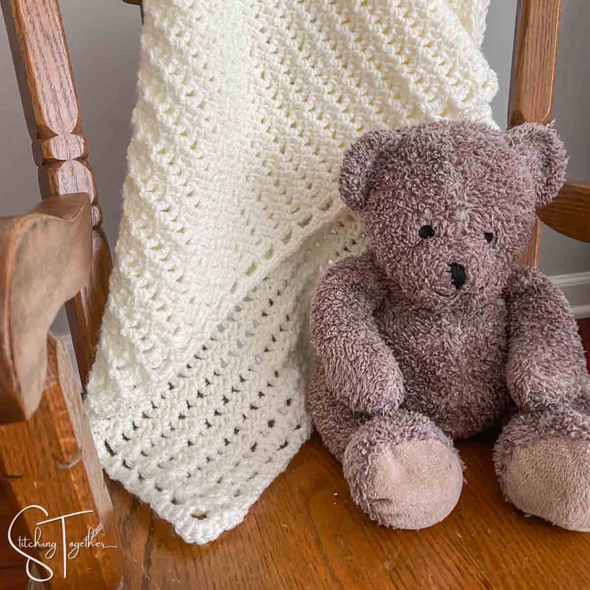 lacy crochet baby blanket draped on chair with stuffed bear next to it