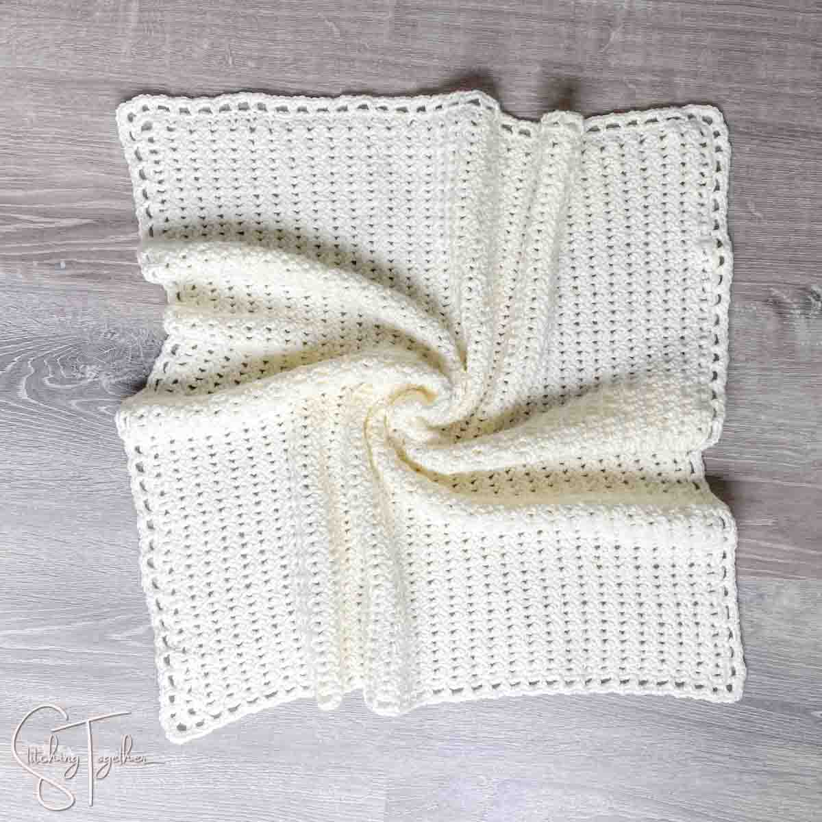 neutral crochet baby blanket laid out on the floor