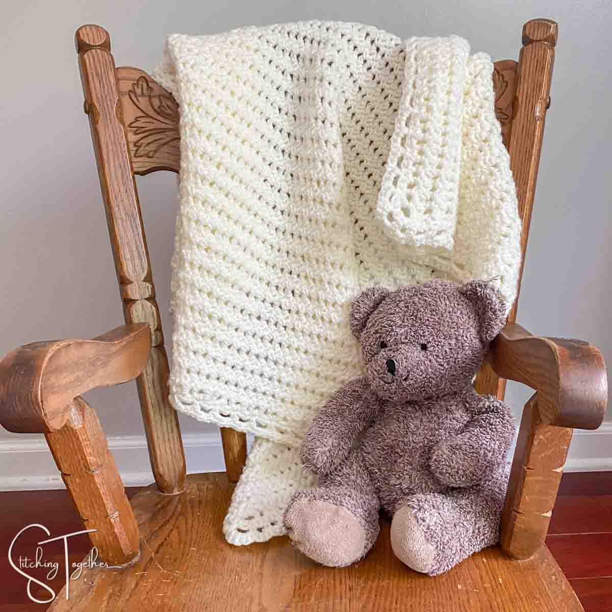 crochet lacy baby blanket draped on chair with stuffed bear next to it