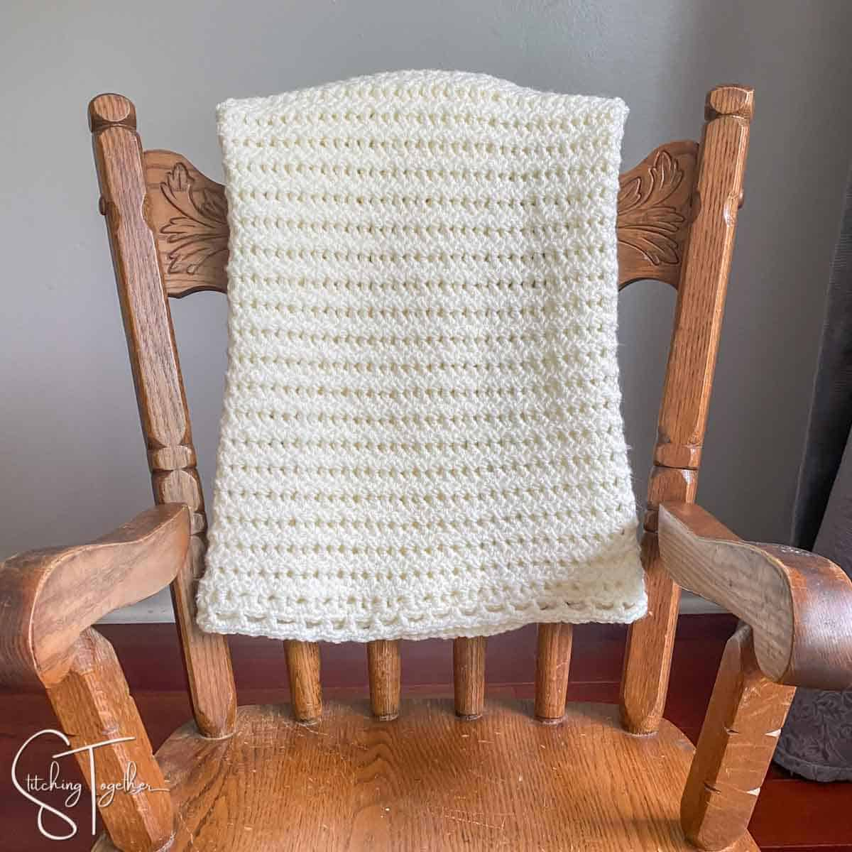 light and lacy crochet baby blanket draped over the back of a small rocking chair