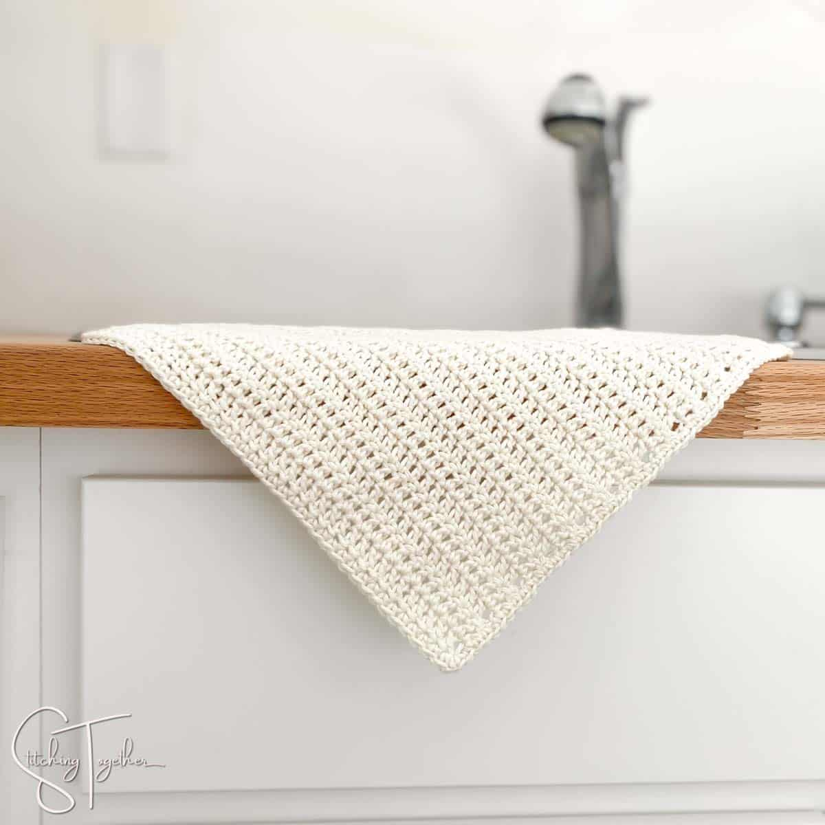 cream crochet dishcloth hanging over the side of the sink