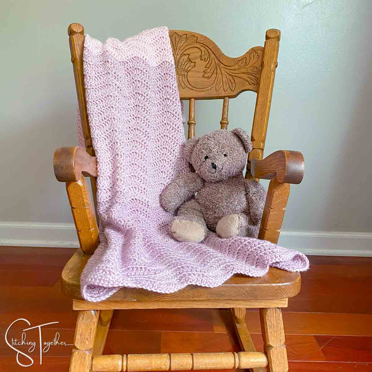 baby blanket ripple crochet draped over a small rocking chair