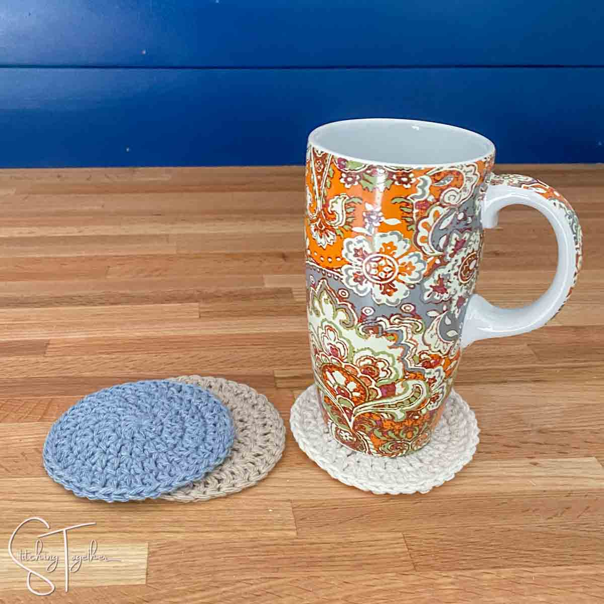 colorful mug sitting on a round crochet coaster with other coaster next to it