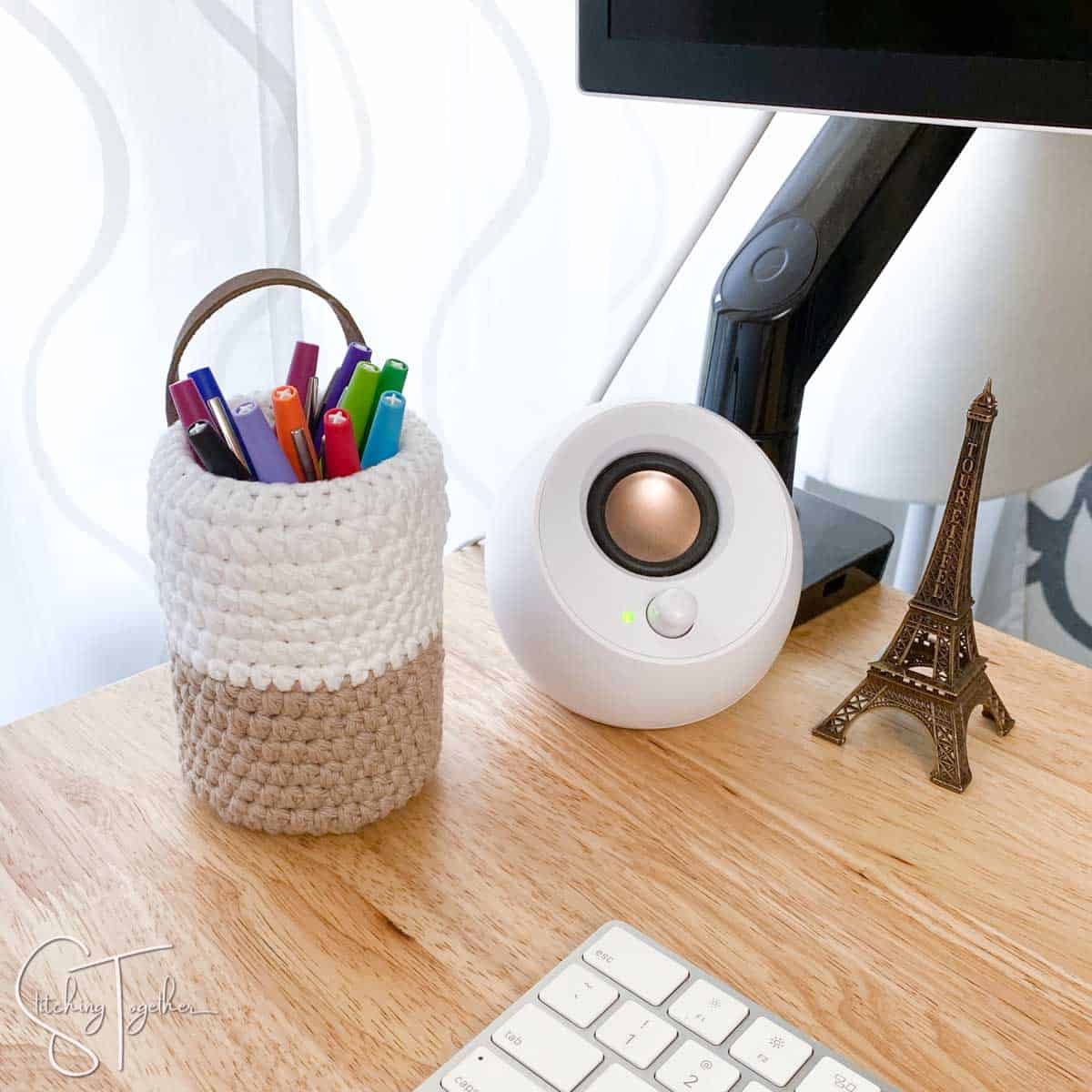 small crochet pen basket filled with colorful pens and sitting on a desk