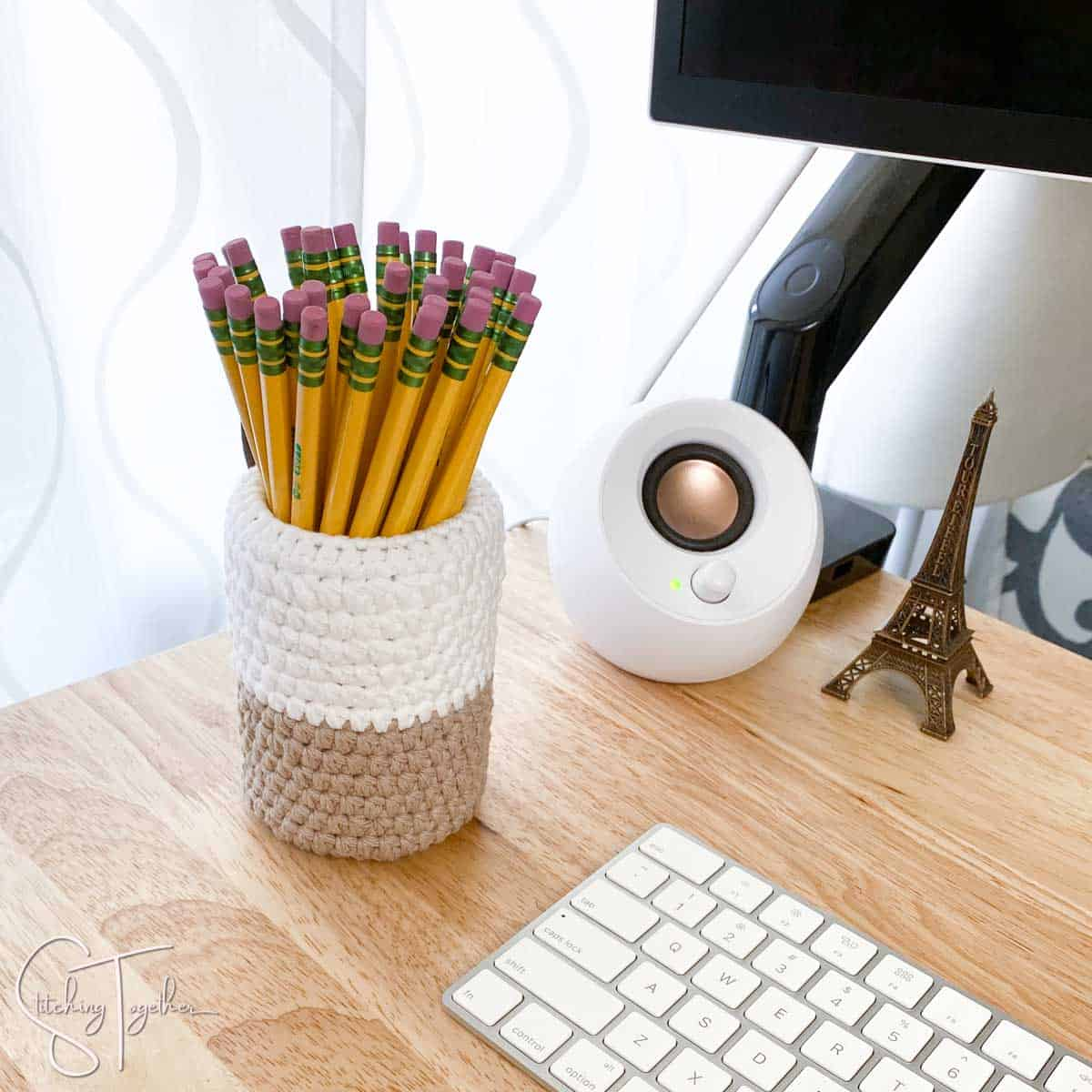 crochet pencil holder filled with pencils and sitting on a desk