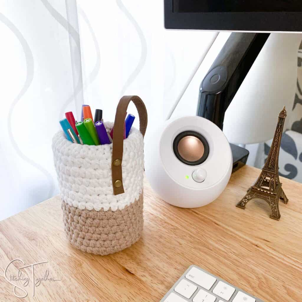 crochet pen holder filled with colorful pens sitting on a desk next to a small speaker