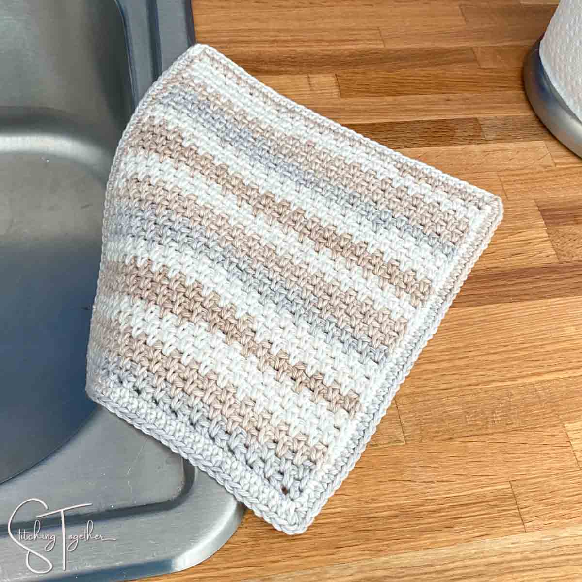 striped crochet moss stitch dishcloth on the side of a sink