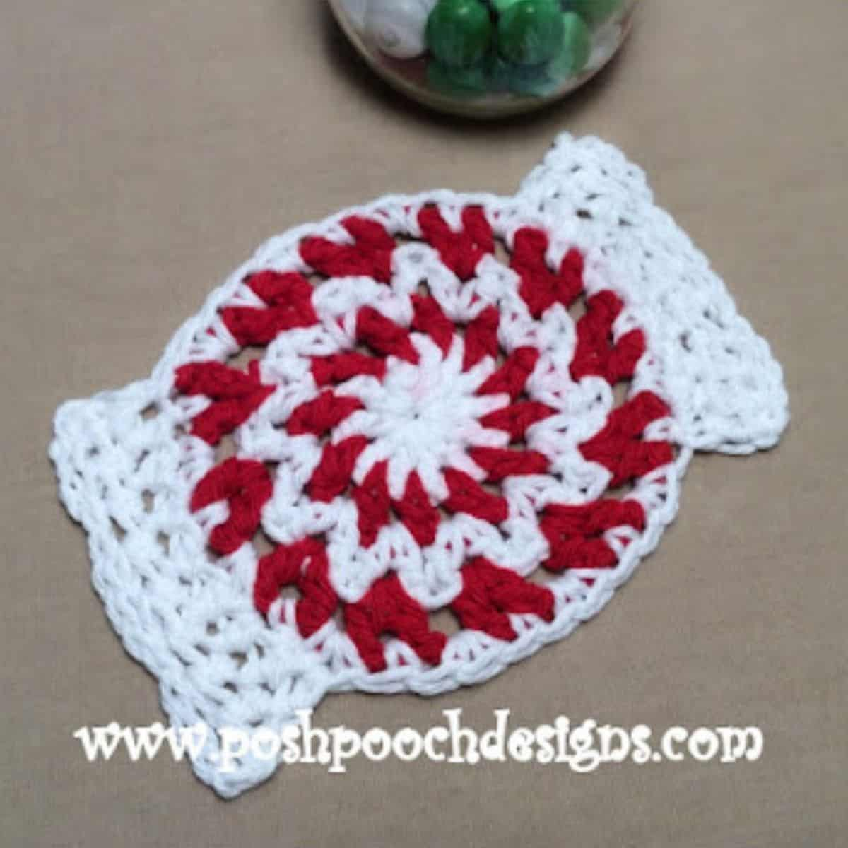 red and white coaster crocheted that looks like a peppermint